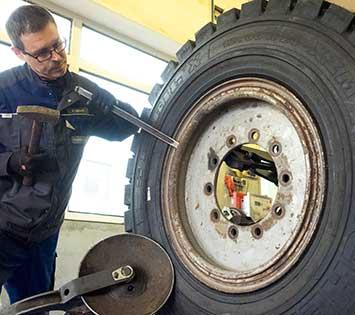 Ein Mitarbeiter der Reifenbörse Arnold montiert einen LKW-Reifen.